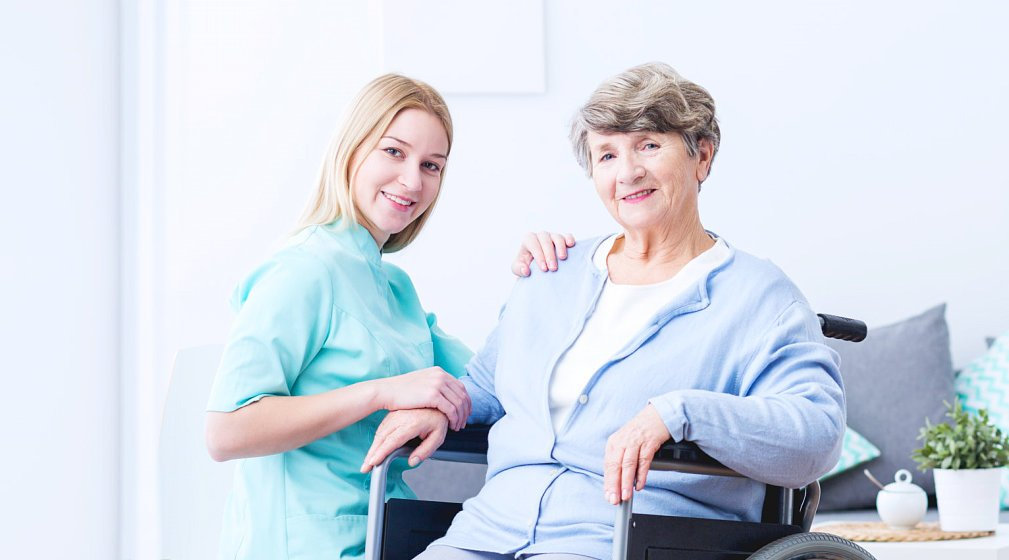 smiling caregiver assisting an old woman