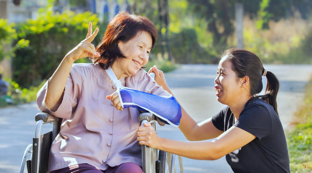 smiling disabled old woman in a wheelchair assisted by her caregiver