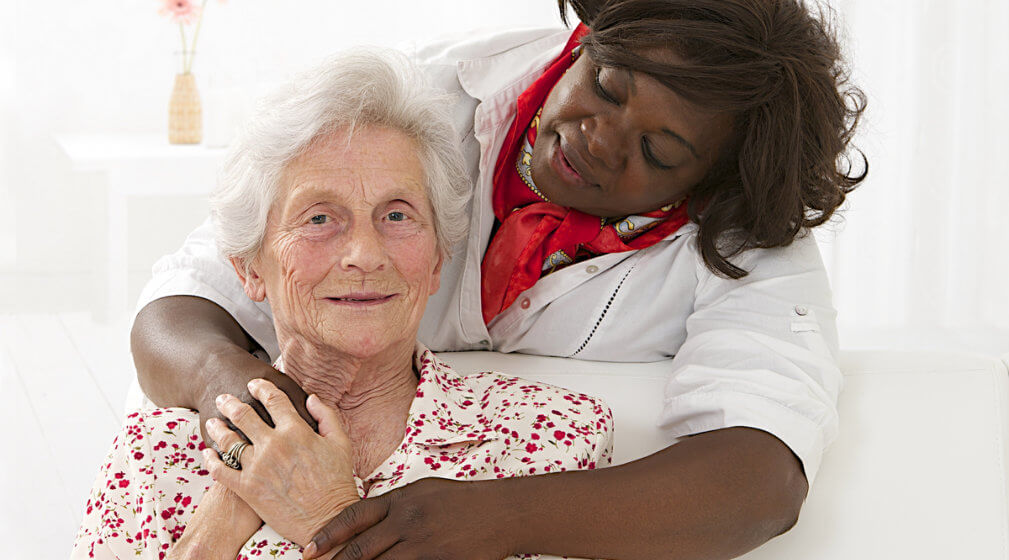 caregiver hugging her old patient