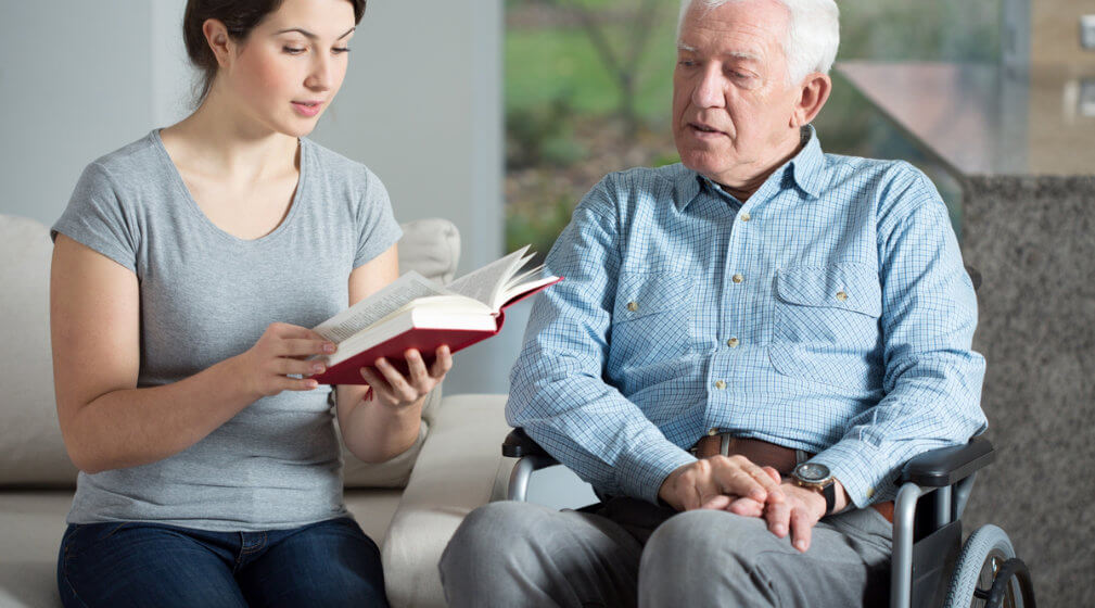 caregiver reading a book for the old man