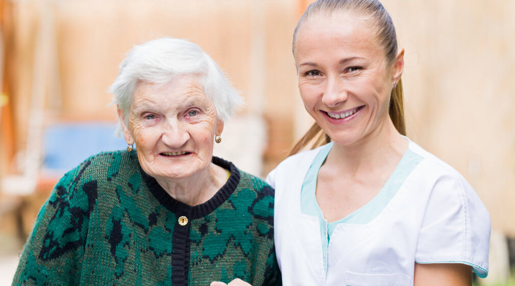 smiling caregiver and her old patient